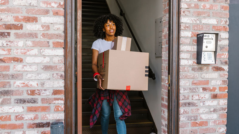 Woman moving a few boxes out the front door of home
